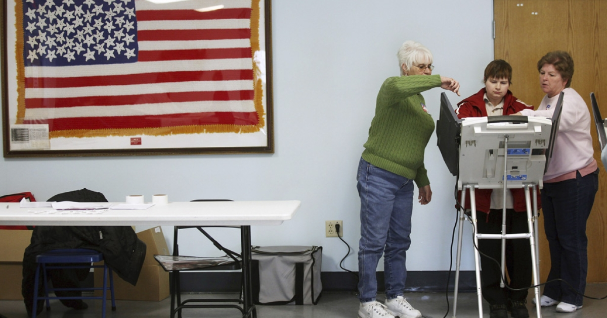 Poll workers assist a voter during Super Tuesday in Carrollton, Ohio. It wasn't until Wednesday morning that CNN declared Mitt Romney the victor over Rick Santorum in Ohio.</p>