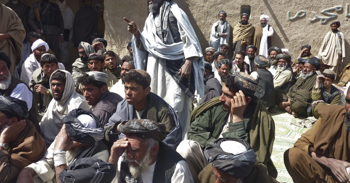 Afghan men gather for a service in Alokozai, Kandahar, on Tuesday for 16 civilians suspected to have been killed on Sunday by a rogue US soldier.</p>