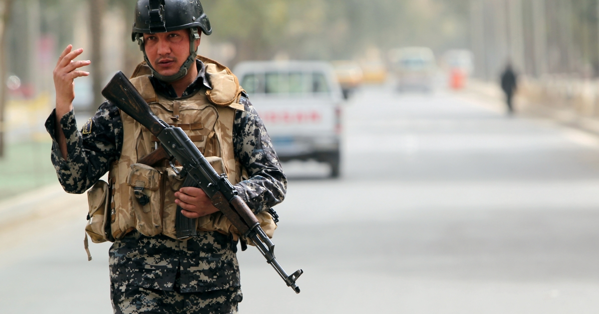 An Iraqi security officer mans a checkpoint in Baghdad.</p>