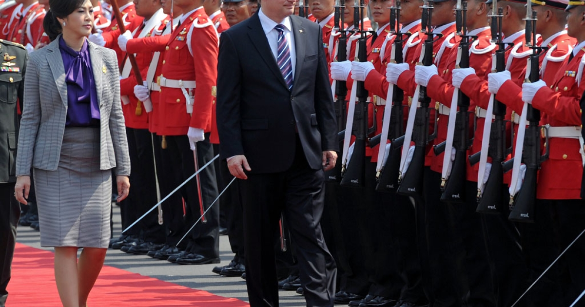 Thai Prime Minister Yingluck Shinawatra, left, and Canada's Prime Minister Stephen Harper review an honor guard at Government House in Bangkok today. Harper is on a 3-day visit to Thailand.</p>