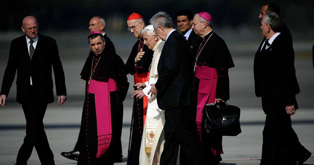 Pope Benedict XVI (C) flanked by Vatican secretary of state Cardinal Tarcisio Bertone (L) and Italian Premier Mario Monti walks with a stick on the tarmac as he boards a plane on his way to Mexico and Cuba on March 23, 2012 at Rome's Fiumicino airport. Pope Benedict XVI sets off on an arduous journey to Latin America where he will address key issues including the war on drugs in Mexico and the evolution of the communist regime in Cuba</p>