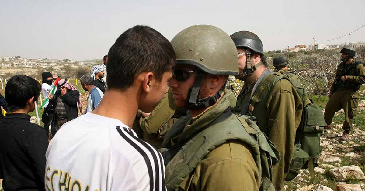 A Palestinian protester confronts an Israeli soldier during a protest after Palestinians and peace activists were prevented by Israeli troops from reaching Palestinian lands in the West Bank village of Beit Omar near the Jewish settlement of Karmei Tzur on March 24, 2012.</p>