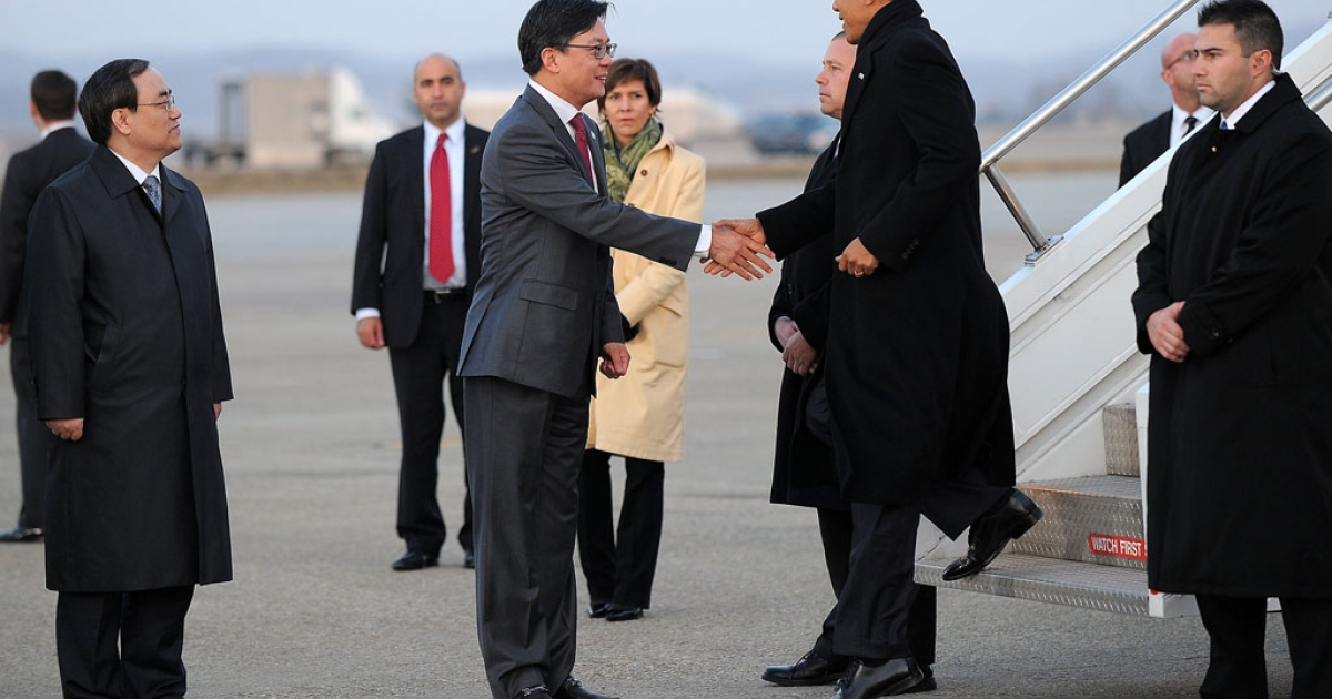 US President Barack Obama meets US ambassador Sung Kim as he disembarks from Air Force One at Osan Air Base in Pyongtaek, some 40 miles south of Seoul, on Sunday.</p>
