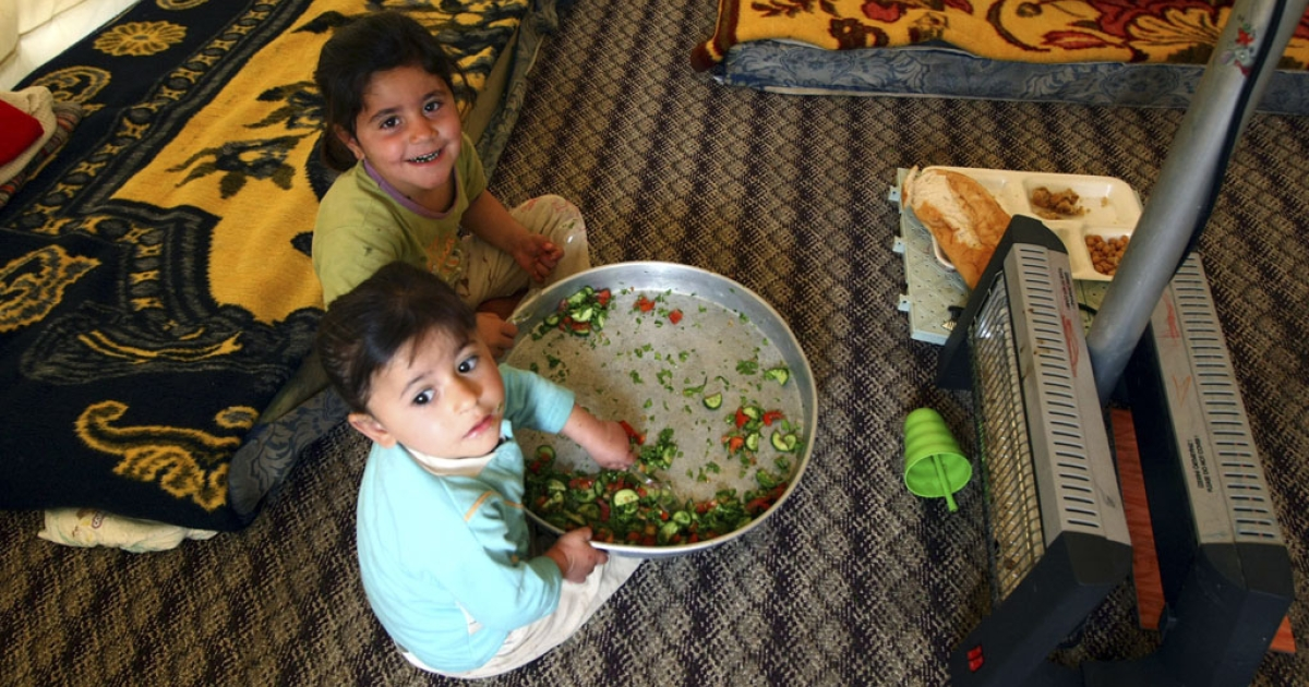 Syrian refugee children eat in a tent at the Red Crescent camp in Boynuyogun, Turkey, near the Syrian border. The Boynuyogun camp holds some 2,000 Syrian refugees in 600 tents.</p>