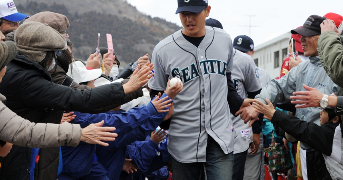 Seattle Mariners pitcher Hisashi Iwakuma greets fans in Ishinomaki, Japan, on Tuesday.  Players from MLB's Seattle Mariners and Oakland Athletics held a baseball clinic and served