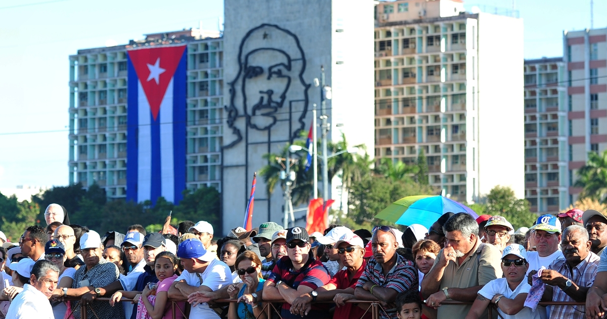 Believers wait for the Pope Benedict XVI nearby a huge portrait of Cuban revolutionary Che Guevara at Revolution Square in Havana, on March 28, 2012.</p>