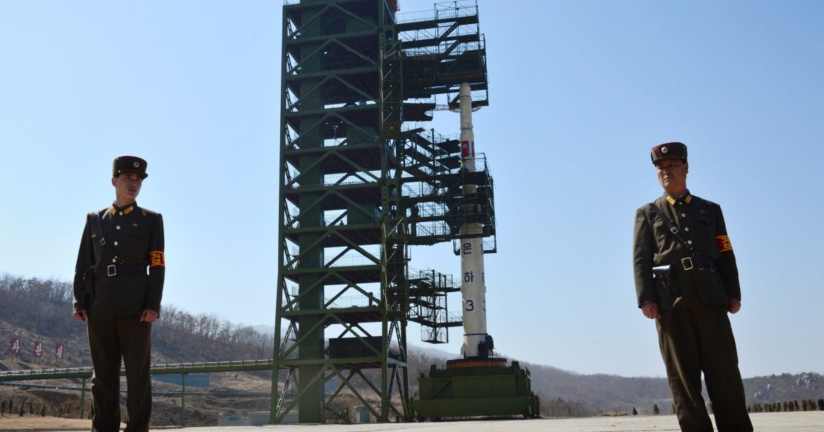 Two North Korean soldiers stand guard in front of the Unha-3 rocket at Tangachai -ri space center on April 8, 2012.</p>
