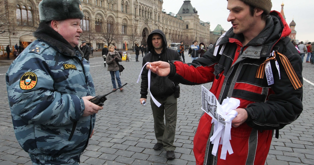 A Russian opposition activist offers a white ribbon, a symbol of opposition, to a police officer during an opposition demonstration at the Red Square in Moscow on April 8, 2012.</p>
