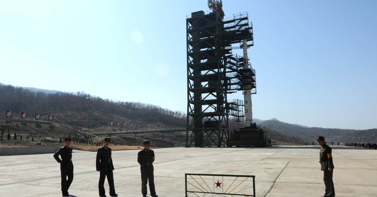 North Korean soldiers stand guard in front of the Unha-3 rocket at Tangachai -ri space center on April 8, 2012.</p>