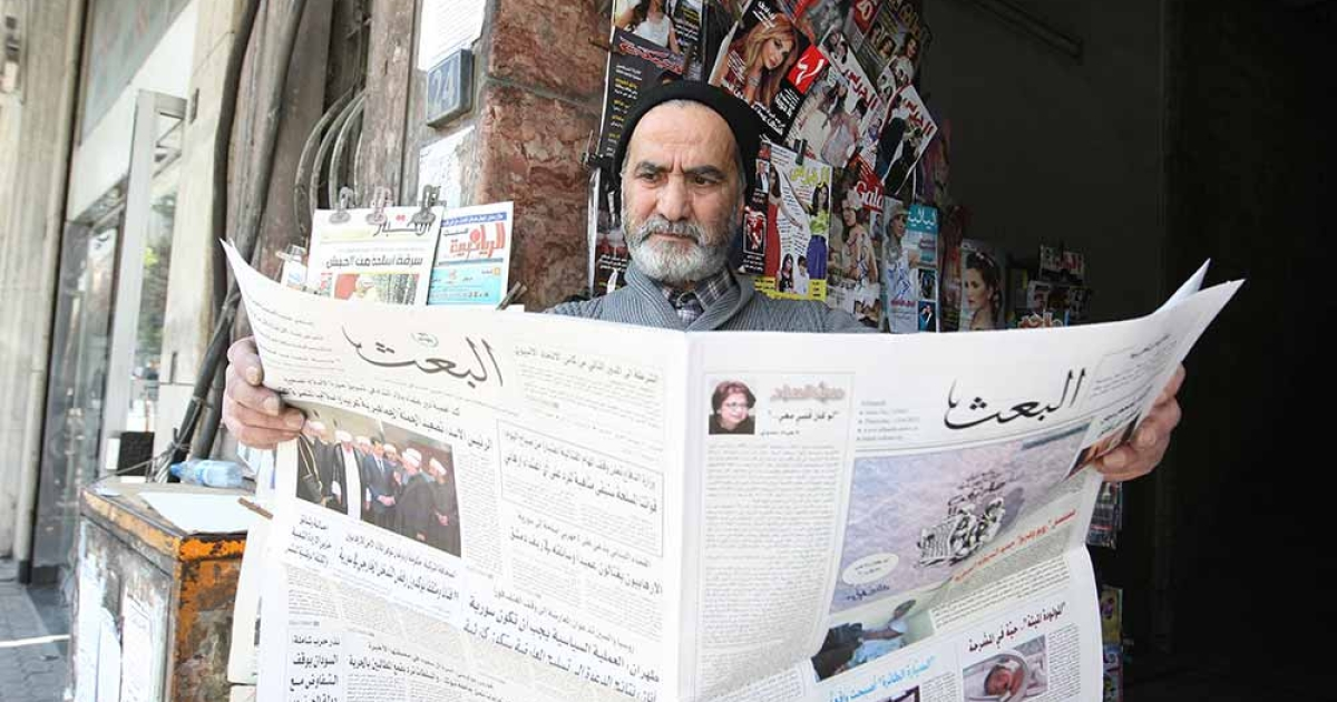A Syrian man reads the local 'Baath' newspaper in Damascus on April 12, 2012, as a UN-backed ceasefire went into effect.</p>