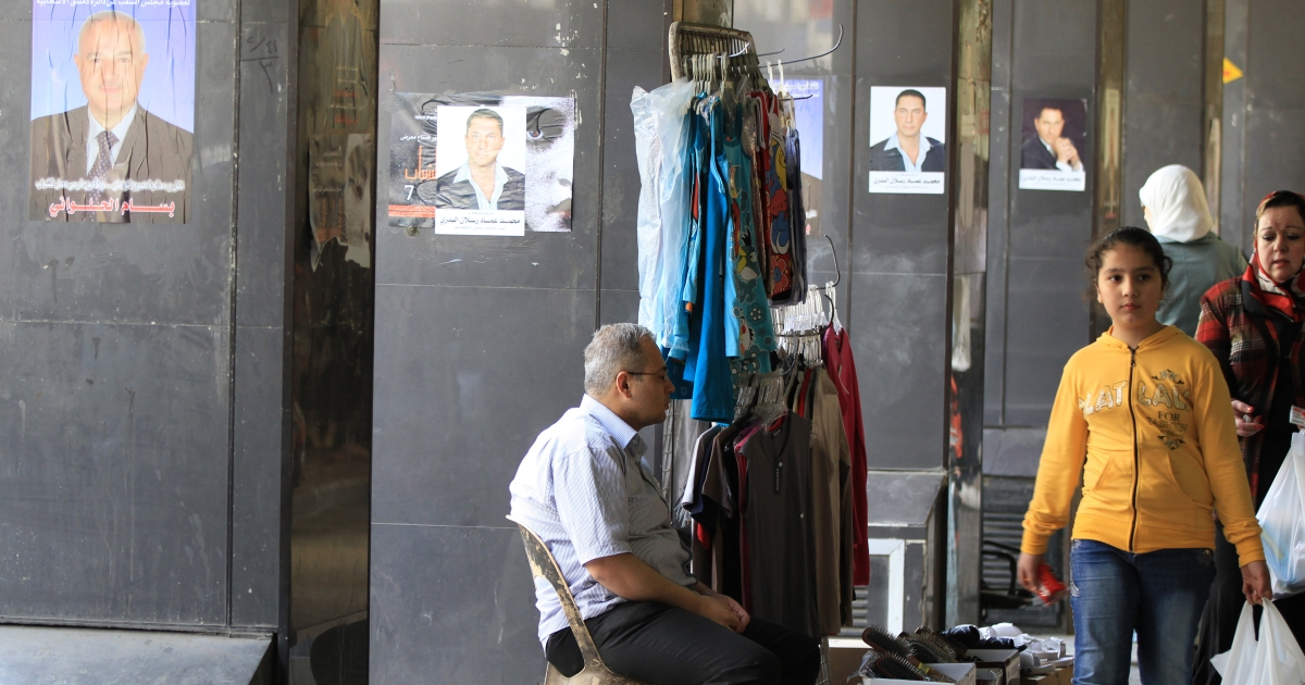 Syrian shoppers walk in front of posters for parliamentary candidates in Damascus on April 12, 2012, as a UN-backed ceasefire went into effect.</p>