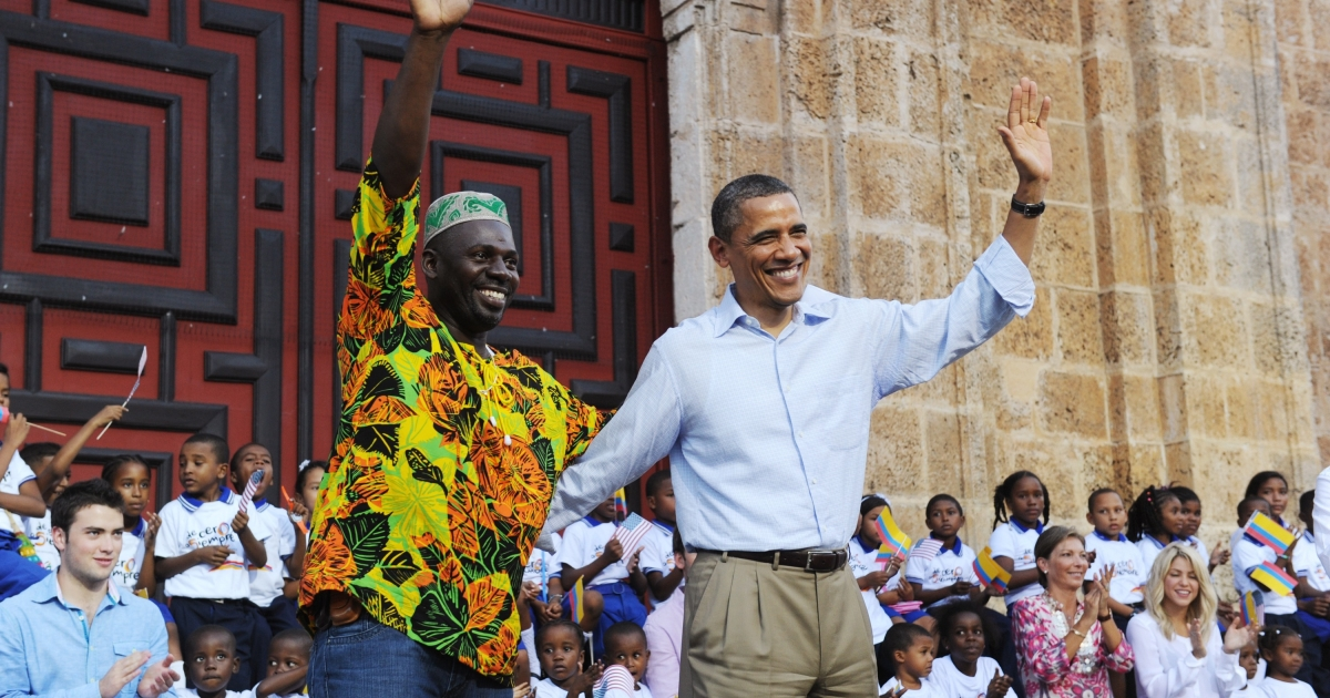 US President Barack Obama (R) waves with a representative of the Afro-Colombia community after he spoke at an event to hand over land titles at the Plaza de San Pedroin Cartagena, Colombia on April 15, 2012 .</p>