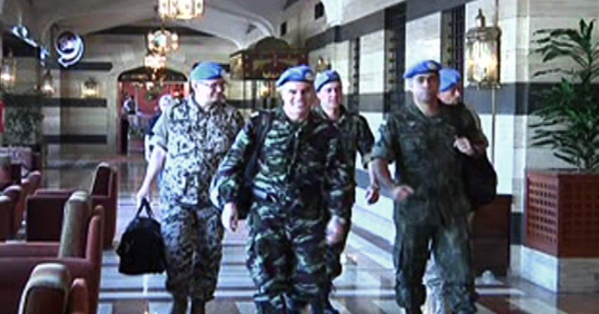 A group UN monitors who arrived in Syria earlier this week walks through the lobby of a Damascus hotel on April 17, 2012.</p>