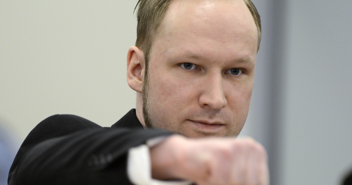Self-confessed mass murderer and right-wing extremist Anders Behring Breivik clenches his fist in a salute as he arrive on day three in room 250 at the central court in Oslo on April 18, 2012.</p>