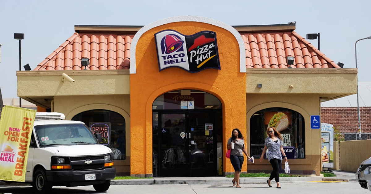 LOS ANGELES, CA - APRIL 19:  Customers walk to a Taco Bell and Pizza Hut restaurant during lunchtime on April 19, 2012 in Los Angeles, California. Yum Brands Inc., the parent company of KFC, Taco Bell and Pizza Hut chains, reported dramatically strong first quarter earnings.</p>