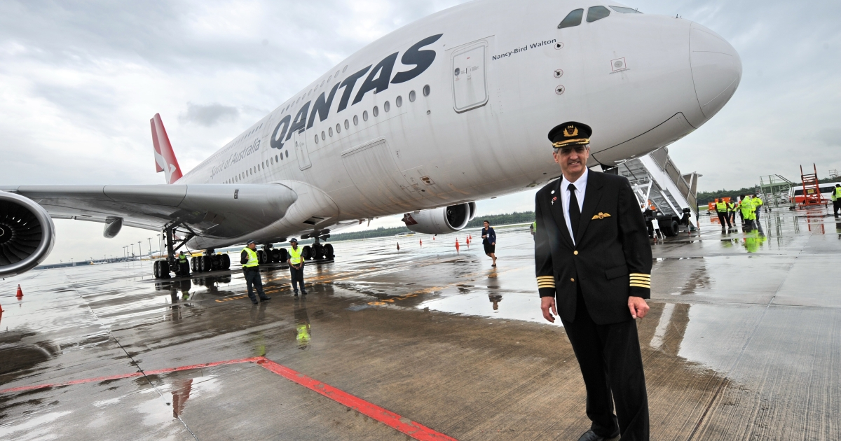Qantas pilot captain Richard de Crespigny poses infront of the Qantas Airbus A380 jet dubbed 'Nancy Bird Walton', in honour of Australia's first female commercial pilot, on the tarmac at the Changi International Airport in Singapore on April 21, 2012. A Qantas Airbus A380 jet that dramatically lost an engine in a mid-air blast off Singapore in November 2010 was formally handed back to the Australian flag carrier April 21 after extensive repairs.</p>