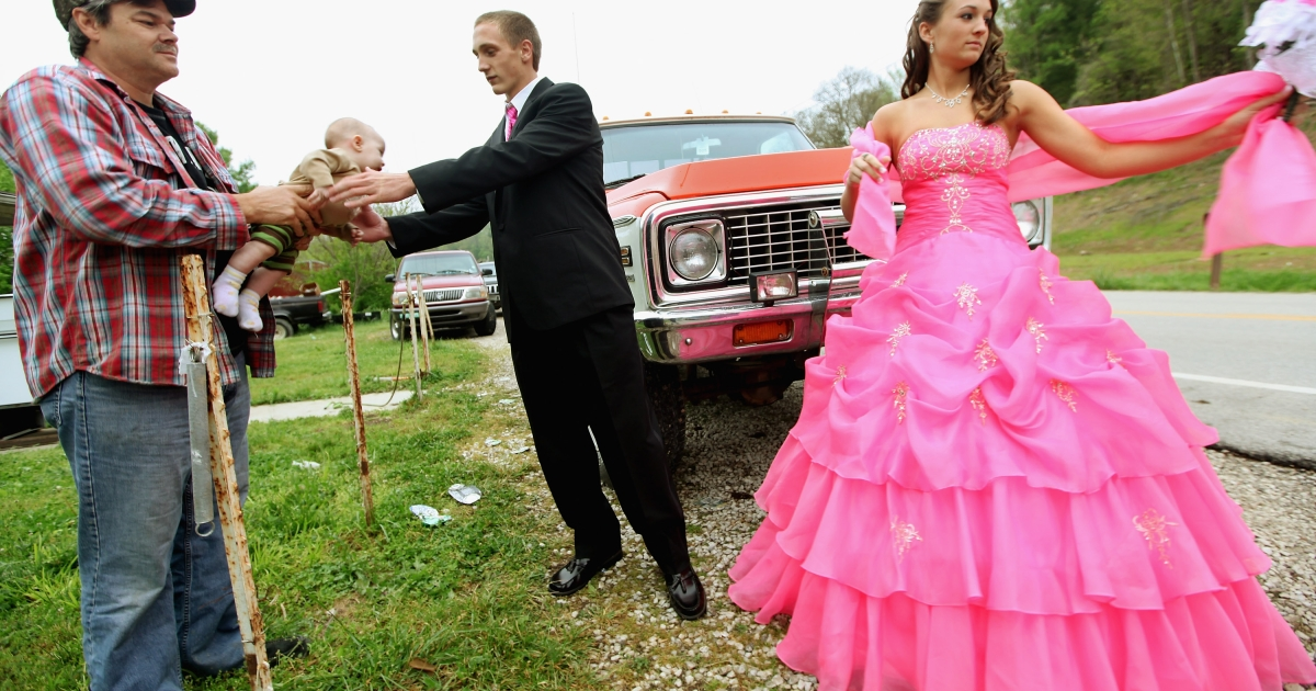 Dates Coty Shouse (C) and Destiny Duff (R) gather as Destiny's father Ronnie Duff (L) passes a baby to be photographed while preparing for the Owsley County High School prom on April 21, 2012 in Booneville, Kentucky.</p>