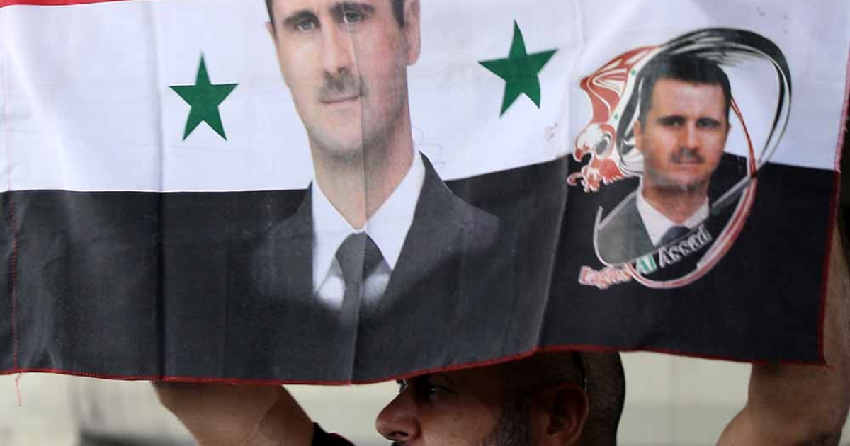A Syrian man holds his national flag bearing pictures of Syrian President Bashar al-Assad during a pro-regime protest to condemn a deadly blast in the central Midan district of Damascus on April 27, 2012.</p>