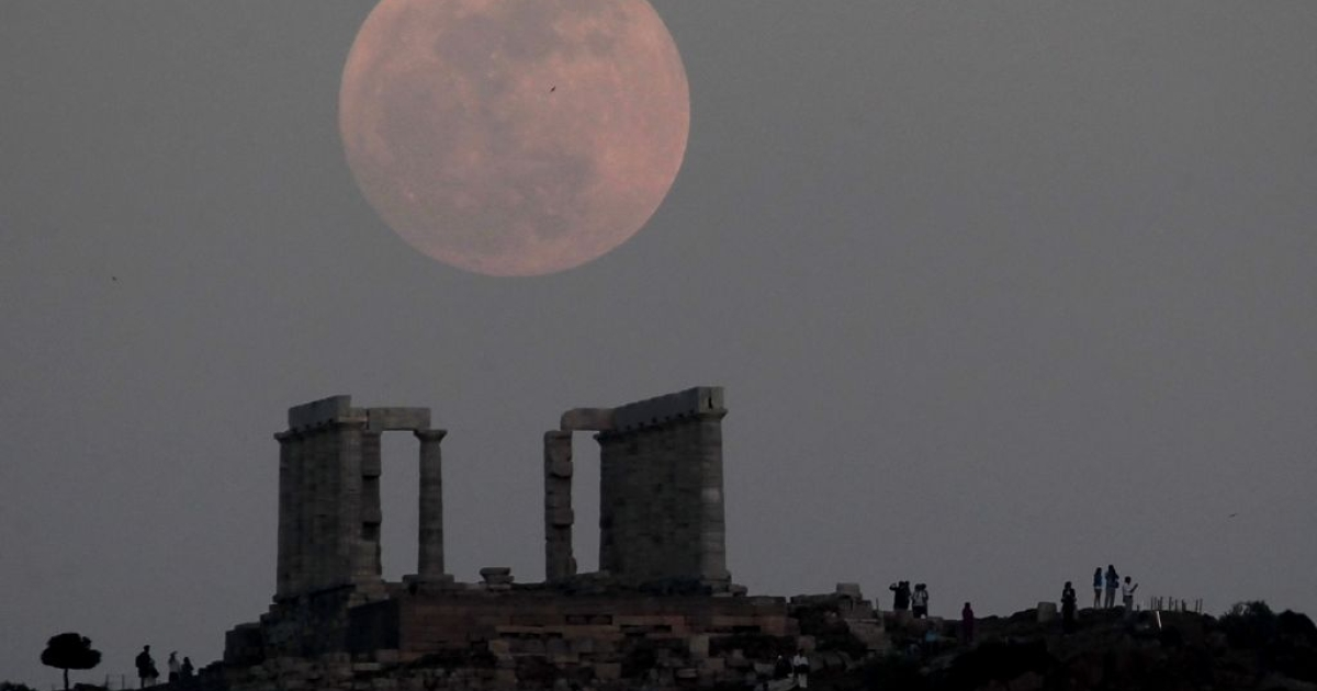 The supermoon rising over the ancient Greek temple of Poseidon at cape Sounion, some 60 kms south of Athens. Due to an unexplained effect known as the