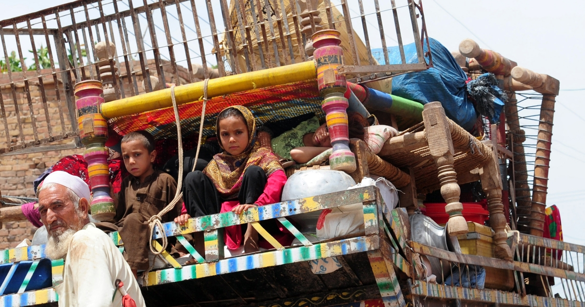 A Pakistani tribal family sit in a mini truck with their belongings as they evacuate from Shlober conflict area, in Bara town of Khyber tribal district on May 7, 2012 following a military campaign launched against the militants.</p>