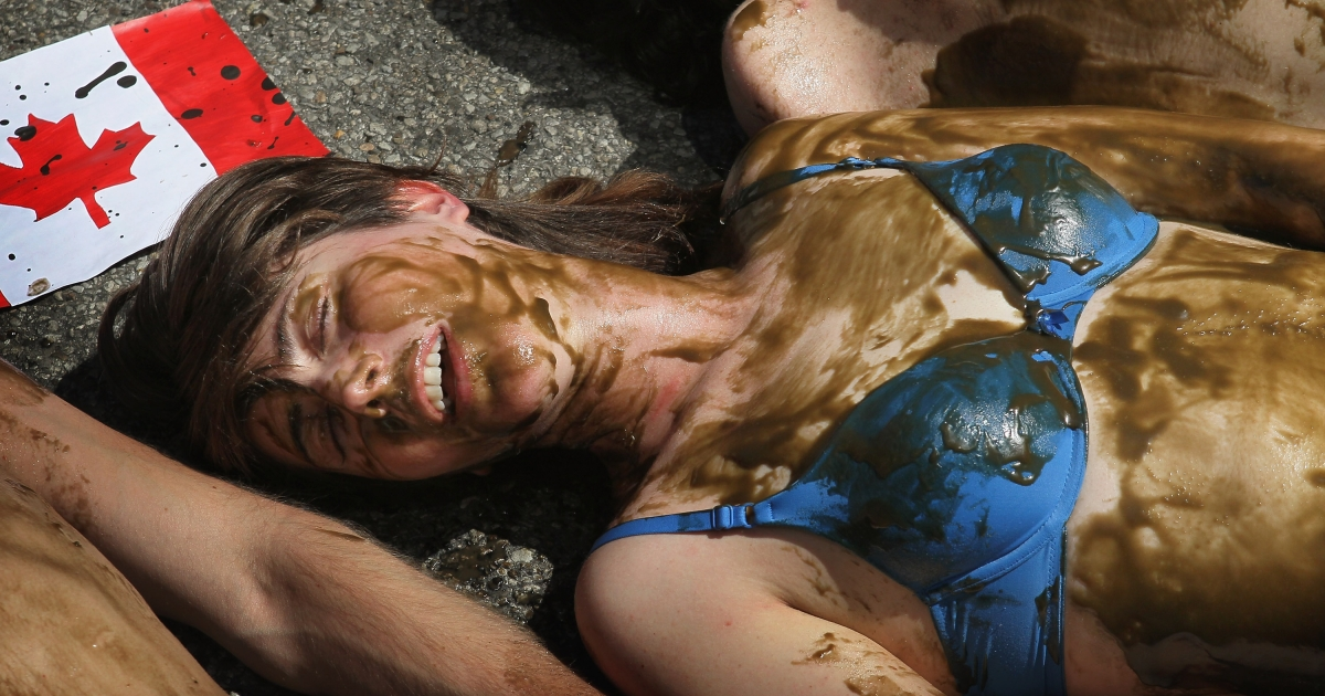 Demonstrators lie in the street covered with an oily substance in front of the Canadian Consulate during a protest against the use of tar sands May 17, 2012 in Chicago, Illinois.</p>