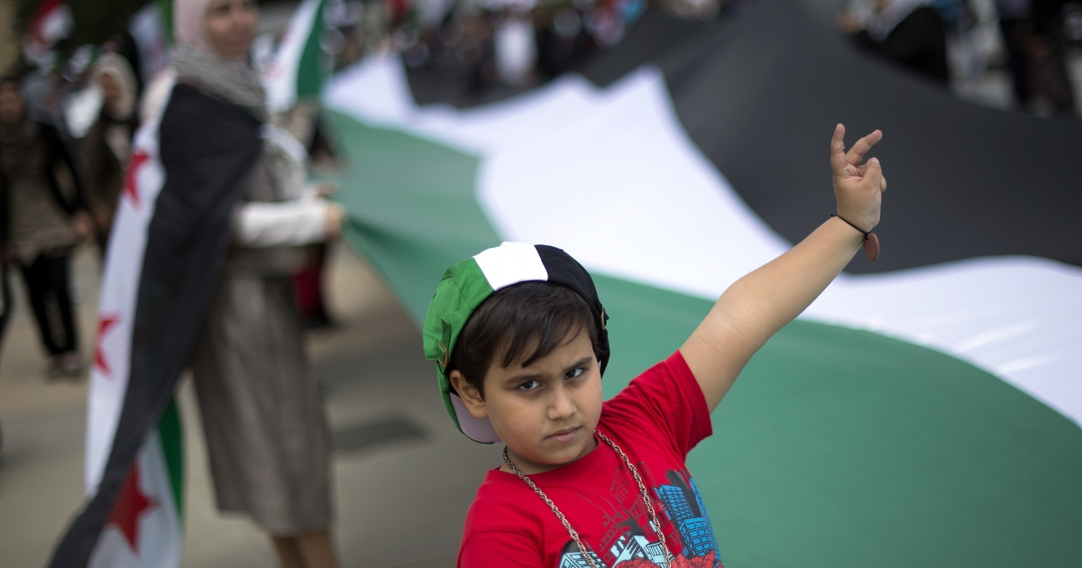 A child flashes a victory sign as he takes part in a European demonstration against the Syrian regime, calling for democracy and an end to bloodshed in Syria, on May 19, 2012, in Geneva.</p>