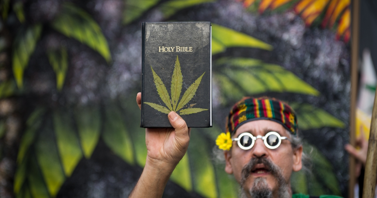 A man holds a Bible with leaves pasted on the cover simulating a marijuana plant during a demo for its legalization in Sao Paulo, Brazil, on May 19, 2012.</p>