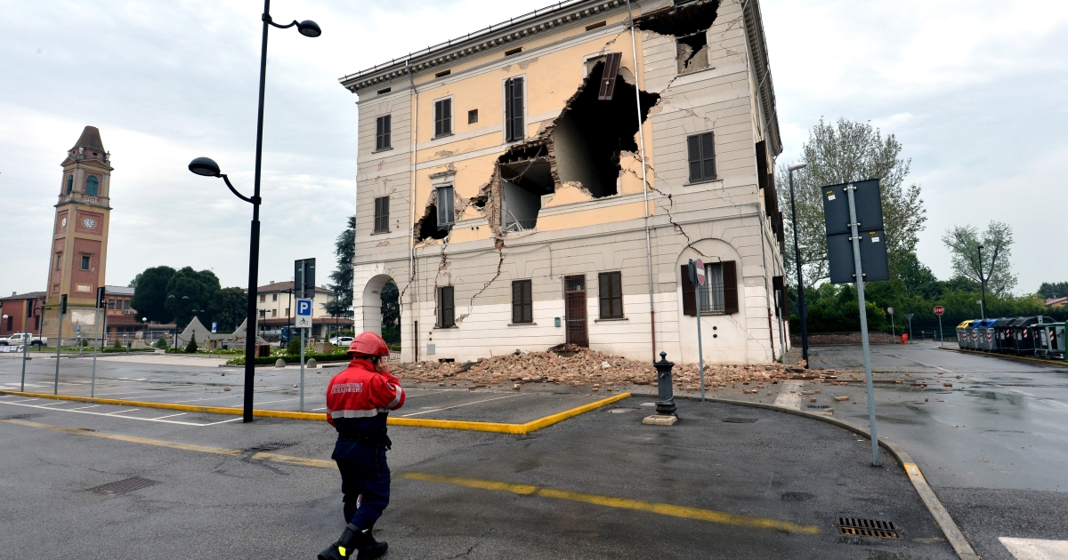 A rescue walks in front of the facade of the town hall after a powerful earthquake that shook Italy's industrial and densely populated northeast early on May 20, 2012 in Sant'Agostino village in the Modena province killing at least six people, felling homes and factories and toppling church steeples.</p>