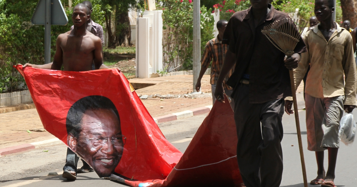 Two Malians drag a portrait of Mali's transition president Diancounda Traore as they take part in a protest with thousands of pro-junta supporters on May 21, 2012 in Bamako.</p>
