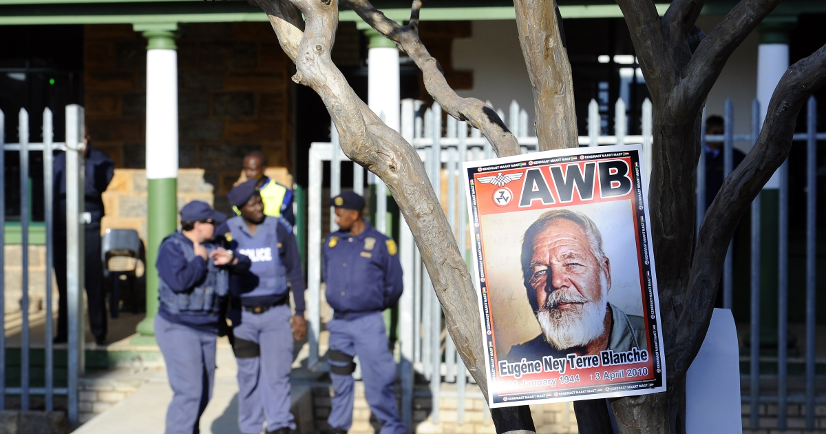 A portrait of white supremacist Eugene Terre'Blanche hangs outside the Ventersdorp Magistrate court before the verdict in his murder trial on May 22, 2012</p>