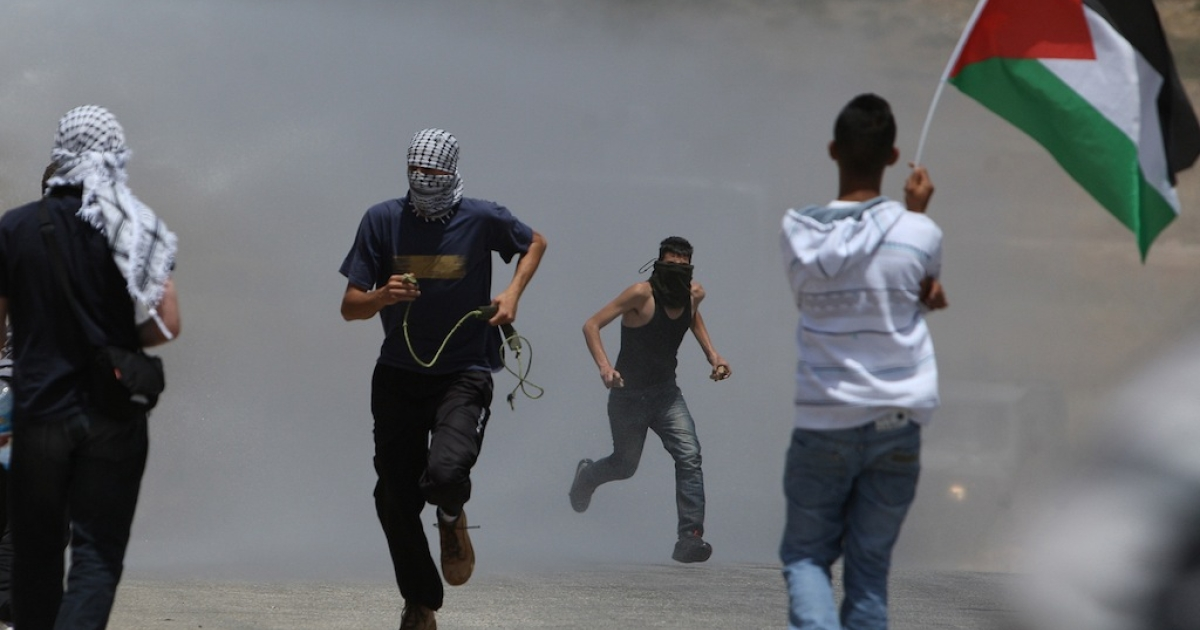 Palestinian youths wave flags and escape tear gas during clashes with Israeli forces following a protest against the confiscation of Palestinian land to expand the nearby Jewish settlement of Hallamish.</p>