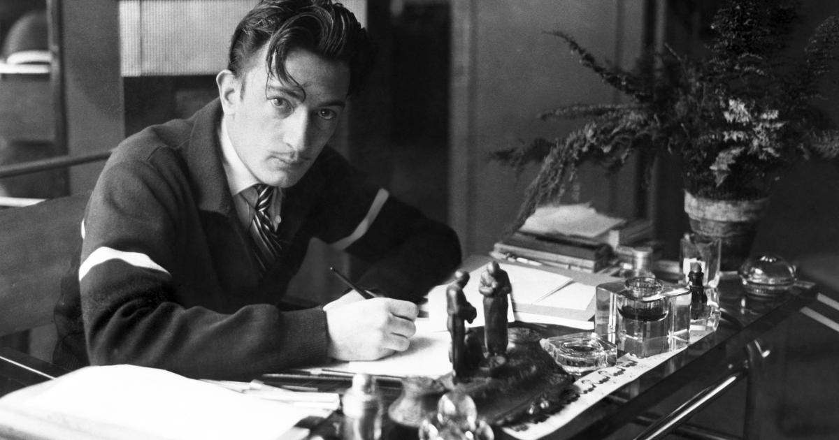 Spanish artist Salvador Dali writing at his desk in the '50s.</p>