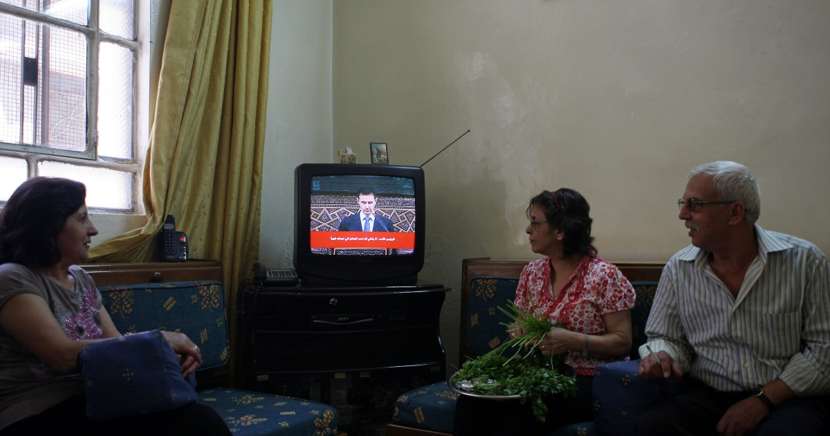 Syrians listen to the televised speech of Syrian President Bashar al-Assad at their house in Damascus on June 3, 2012.</p>