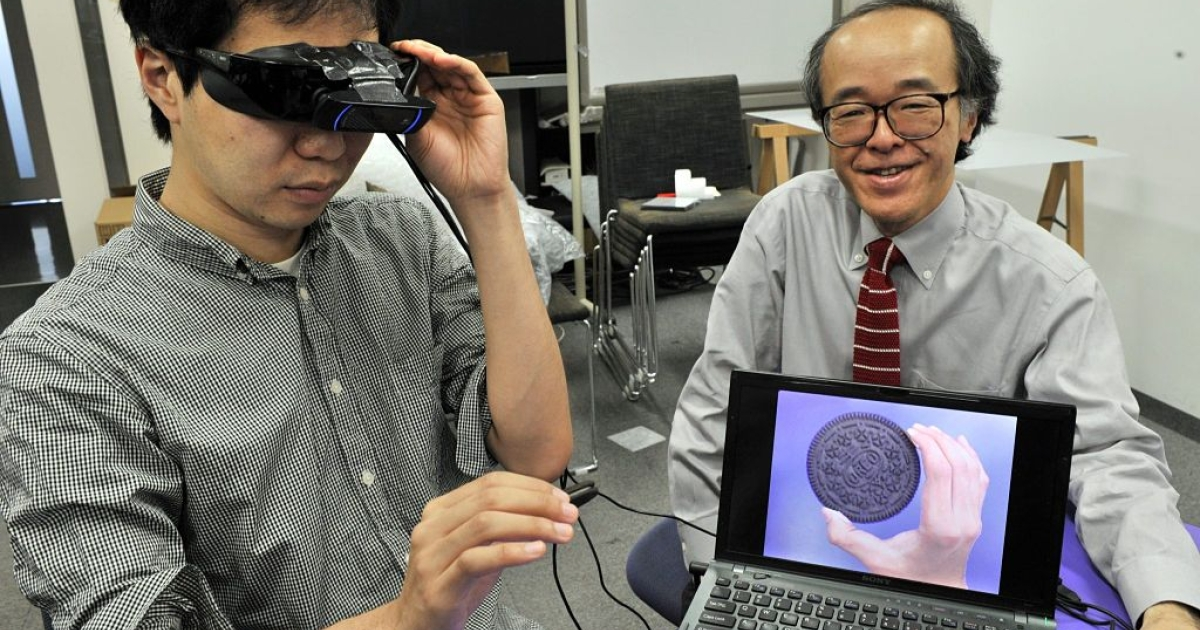 Tokyo University professor Michitaka Hirose (R) and his team developed a camera-equipped special goggle, which makes cookies bigger to help users' diet at his laboratory in Tokyo on June 2, 2012. Hirose conducted an experiment, asking examinees to eat as many cookies as they want with and without the glasses. The results showed they ate 9.3 percent less on average with the goggle showing cookies 1.5 times bigger than they actually are and ate 15 percent more with cookies looking two-thirds of their real size.</p>