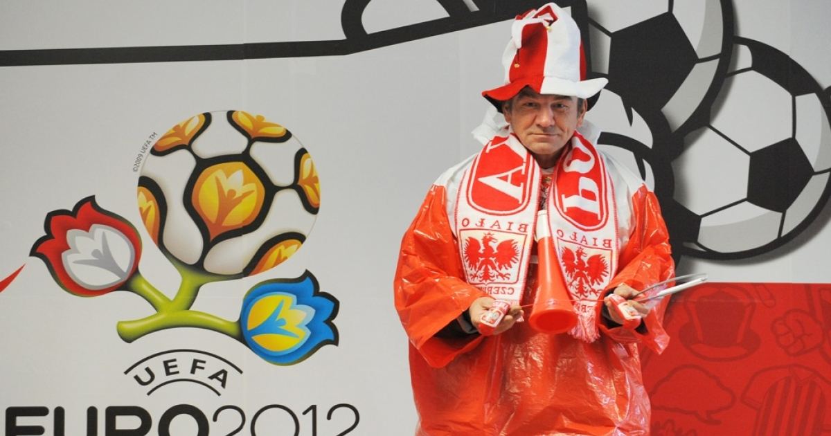 A Polish fan outfits seller stands next to a UEFA Euro 2012 tournament banner downtown Wroclaw on June 5, 2012 ahead of the Euro 2012 football championships which will start on June 8 in Warsaw.</p>