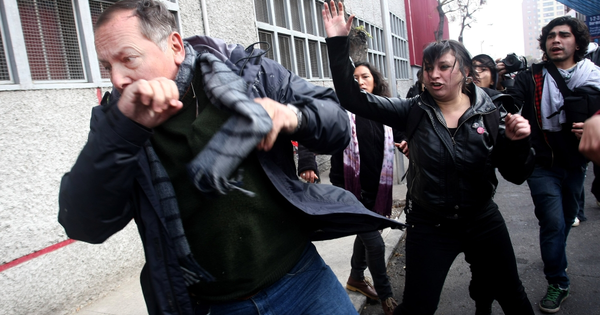 Opponents and sympathizers of late Chilean dictator (1973-90) general Augusto Pinochet scuffle in front of the Caupolican Theatre in Santiago, on June 10, 2012.</p>