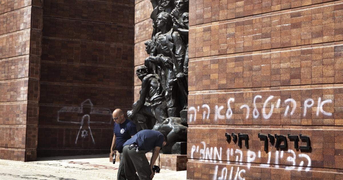 Israeli policemen inspect anti-Zionist Hebrew graffiti some thanking Hitler for the Holocaust and denouncing Zionism was sprayed at Jerusalem's Yad Vashem Holocaust museum compound June 11, 2012 in Jerusalem.</p>
