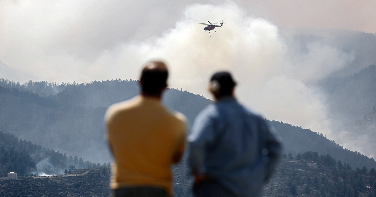 A Sikorsky S-64 Aircrane firefighting helicopter circles as it prepares to drop water on a hotspot near Horsetooth Reservoir on Monday June 11, 2012 near Laporte, Colorado.</p>