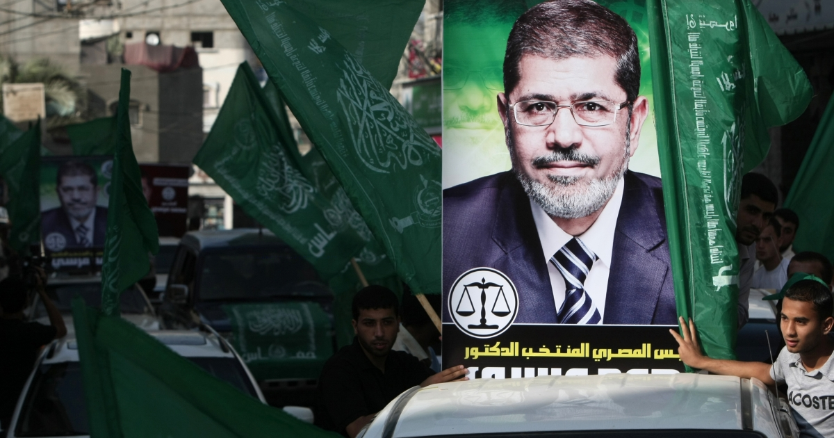 Palestinian Hamas supporters celebrate in the streets of Jabalia refugee camp in the northern Gaza Strip after Egyptian Muslim Brotherhood candidate Mohammed Mursi (portraits) claimed victory in the presidential race, on June 18, 2012.</p>