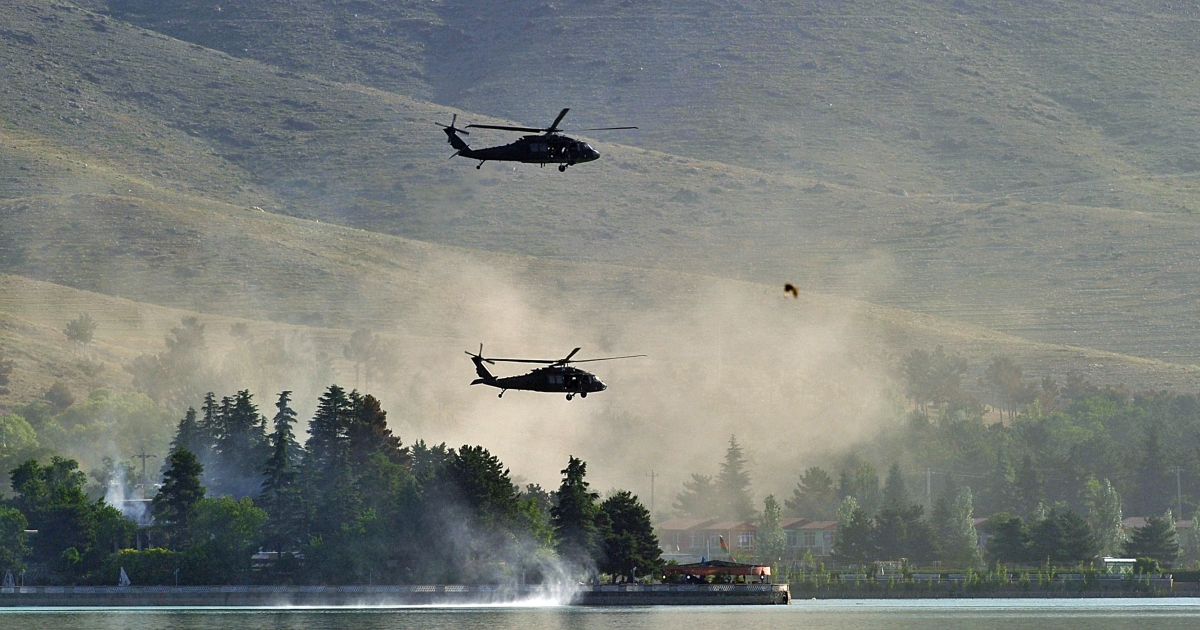NATO UH-60 Black Hawk helicopters fly near the Spozhmai Hotel in Qargha lake in the outskirts of Kabul on June 22, 2012.</p>