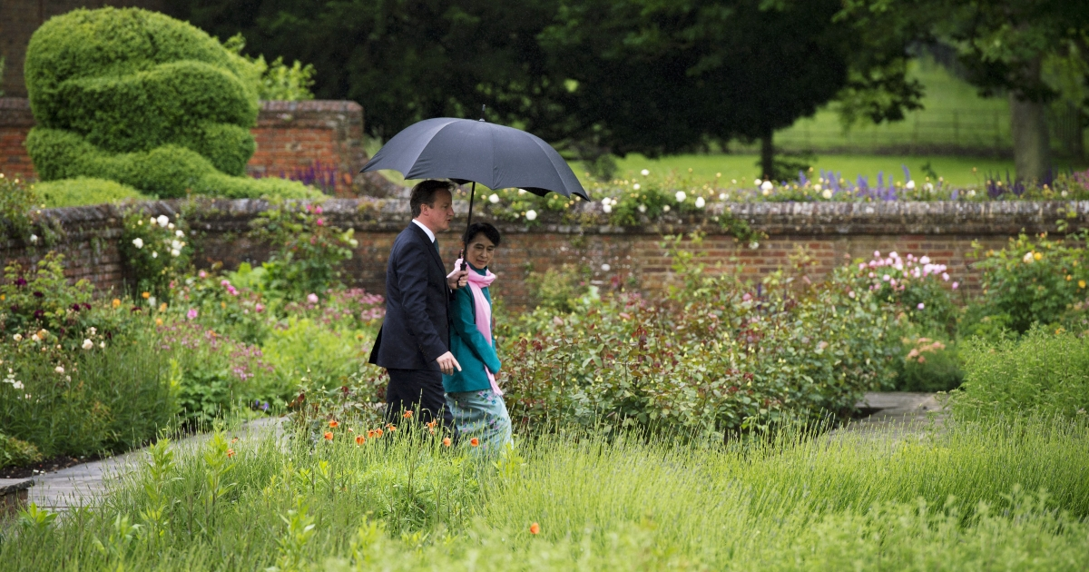 Britain's Prime Minister David Cameron (L) speaks with Myanmar democracy icon Aung San Suu Kyi as they walk in the rose garden at Chequers, the Prime Minister's official country residence, in Buckinghamshire, west of London, on June 22, 2012.</p>