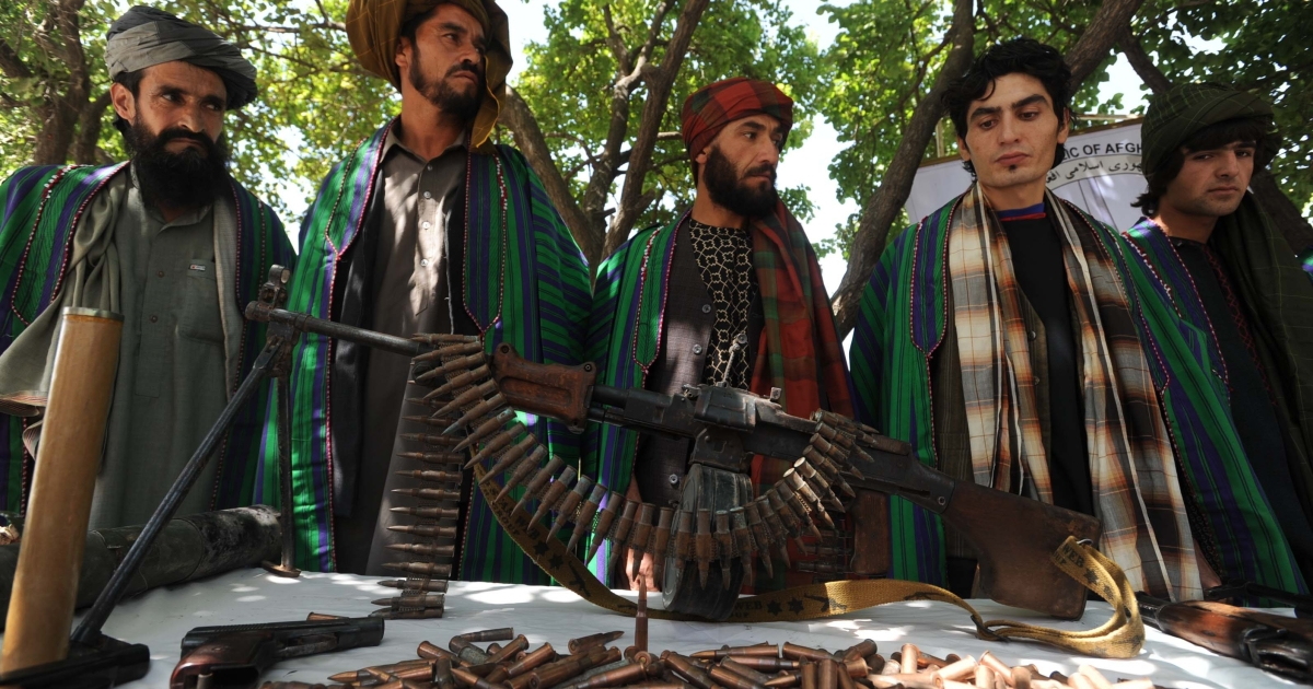 Former Taliban fighters display their weapons as they join Afghan government forces during a ceremony in Herat province on June 23, 2012. Ten fighters left the Taliban to join government forces in western Afghanistan.</p>