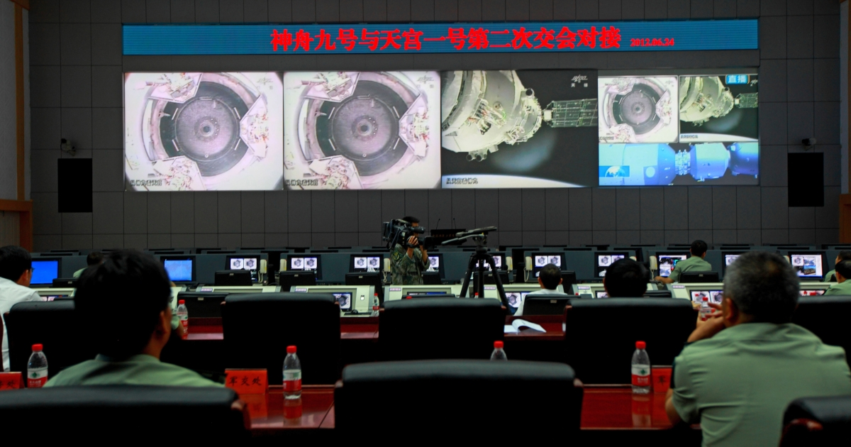 Chinese technicians at the Jiuquan Space Centre monitor the Shenzhou-9 spacecraft as it prepares to link with the Tiangong-1 module just over a week into a manned space mission which includes China's first female astronaut, following an automatic docking, on June 24, 2012.</p>