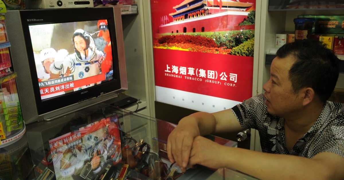 A shop owner watches television in his store in Shanghai as China's first female astronaut Liu Yang is shown getting out of the return capsule of the Shenzhou-9 spacecraft after returning to earth on June 29, 2012.</p>