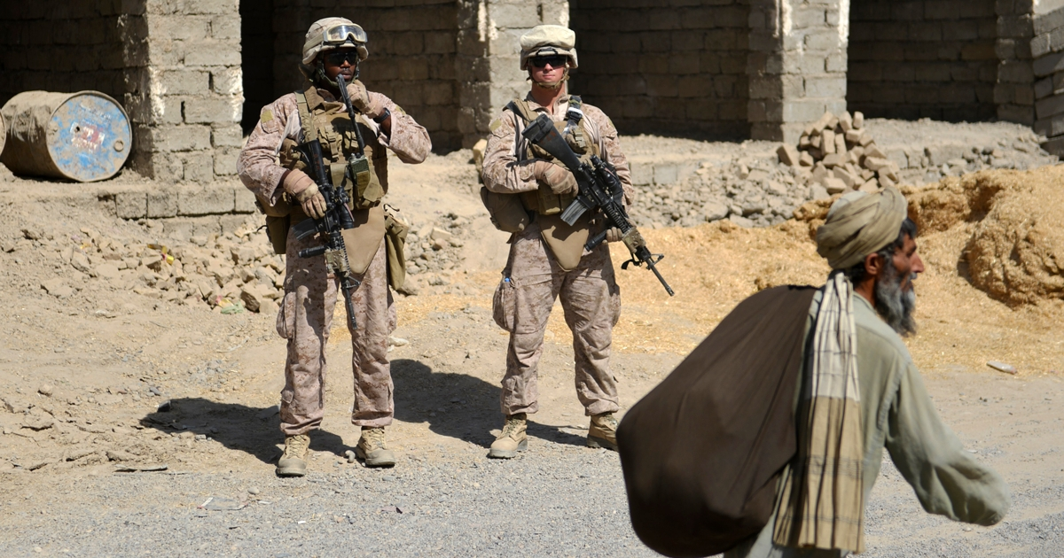 An elderly Afghan walks past US Marines from Kilo Company of the 3rd Battalion 8th Marines Regiment while they conduct a patrol in Garmser, Helmand Province on June 29, 2012.</p>
