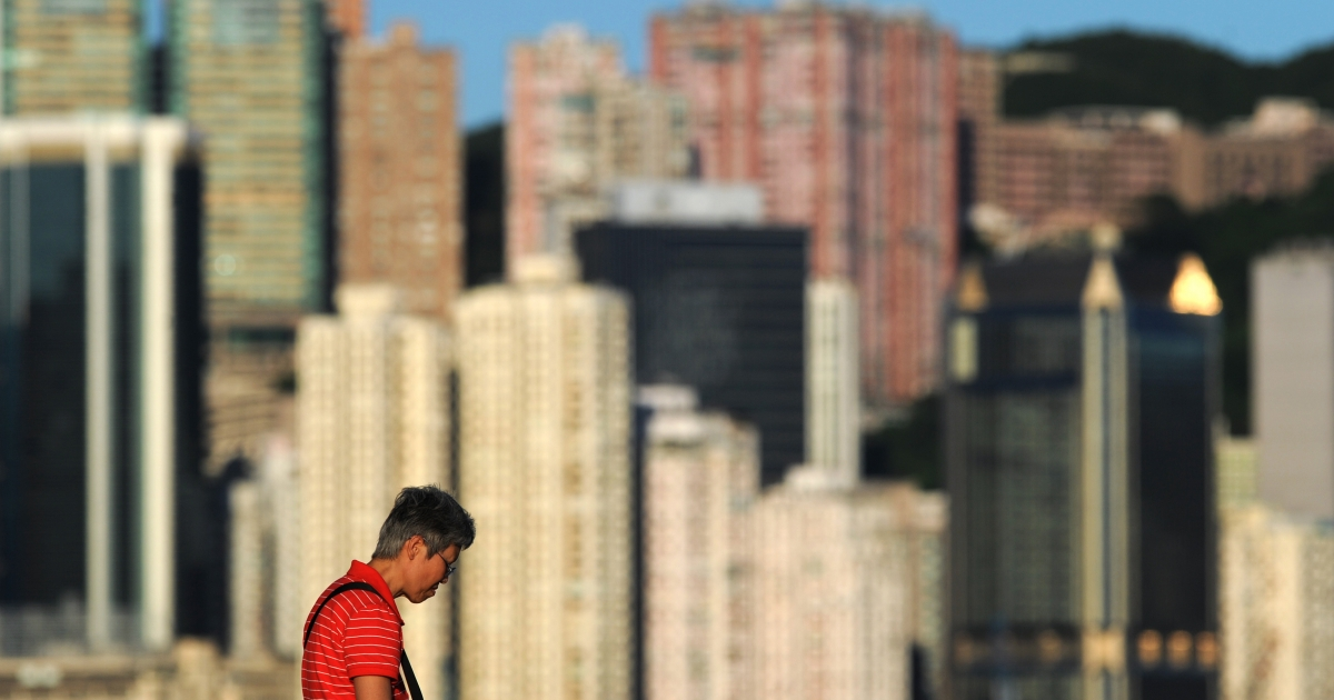 A woman reads a book before residential and commercial buildings in Hong Kong on July 3, 2012.</p>
