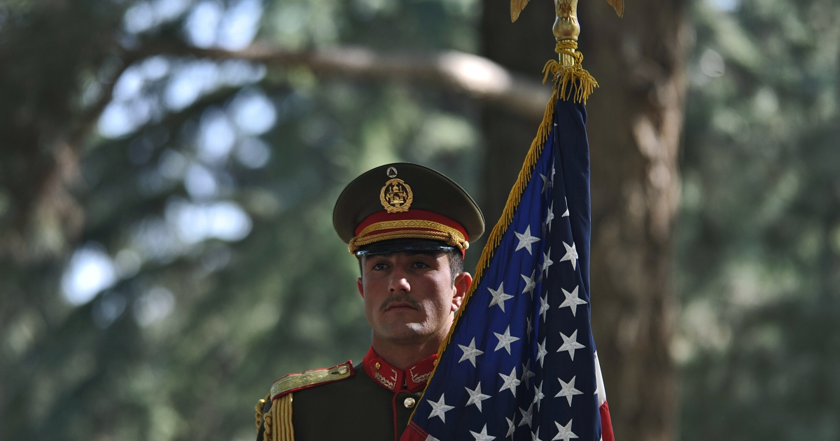 An Afghan military serviceman holds the US flag during a press conference attended by Afghan President Hamid Karzai and US Secretary of State Hillary Clinton at the Presidential Palace in Kabul on July 7, 2012.</p>