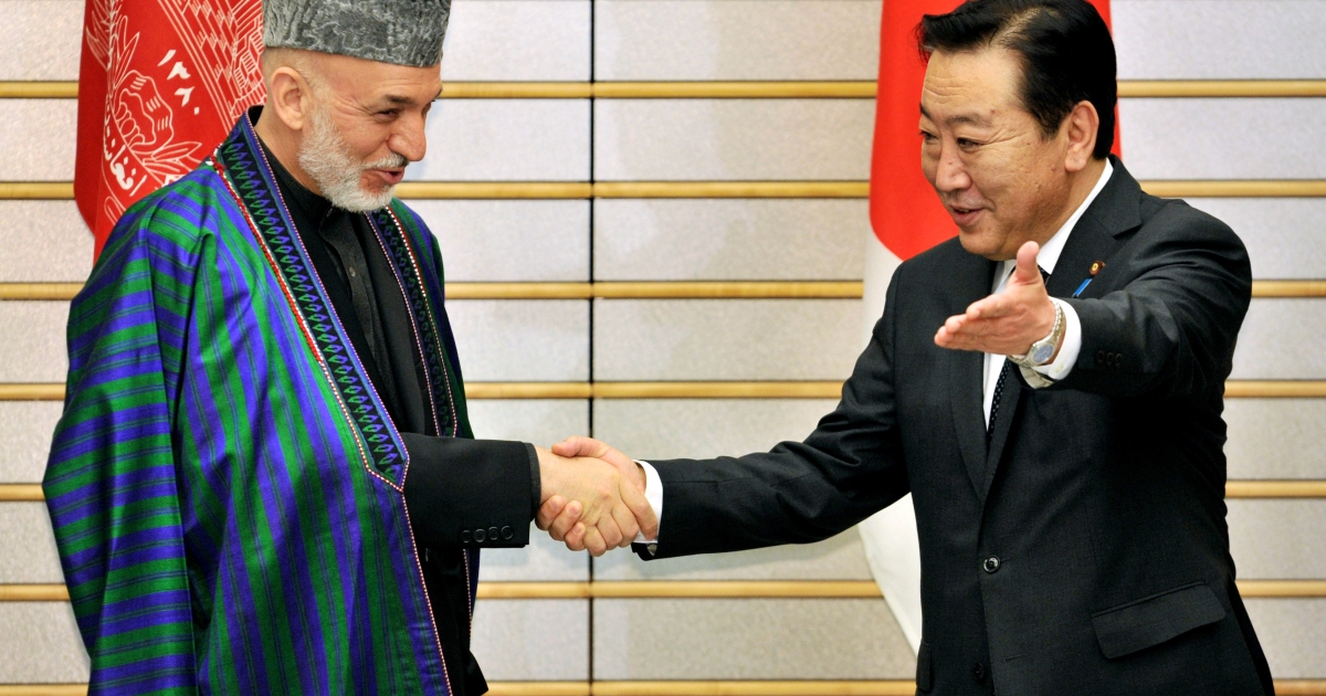 Afghan President Hamid Karzai (L) is greeted by Japanese Prime Minister Yoshihiko Noda for their talks at Noda's office in Tokyo on July 9, 2012.</p>