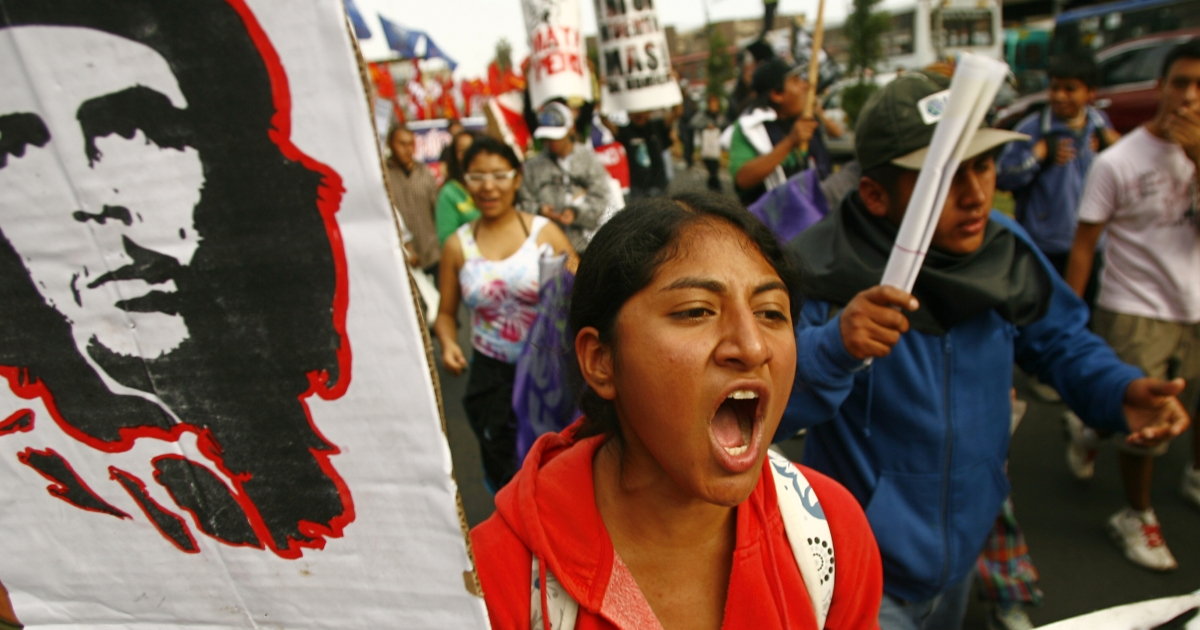 A woman holding a banner with the portrait of Argentine-born revolurtionary leader Ernesto 'Che' Guevara, shouts slogans as she takes part in a protest against the Conga mining project of US corporation Newmont, in Lima on July 12, 2012.</p>