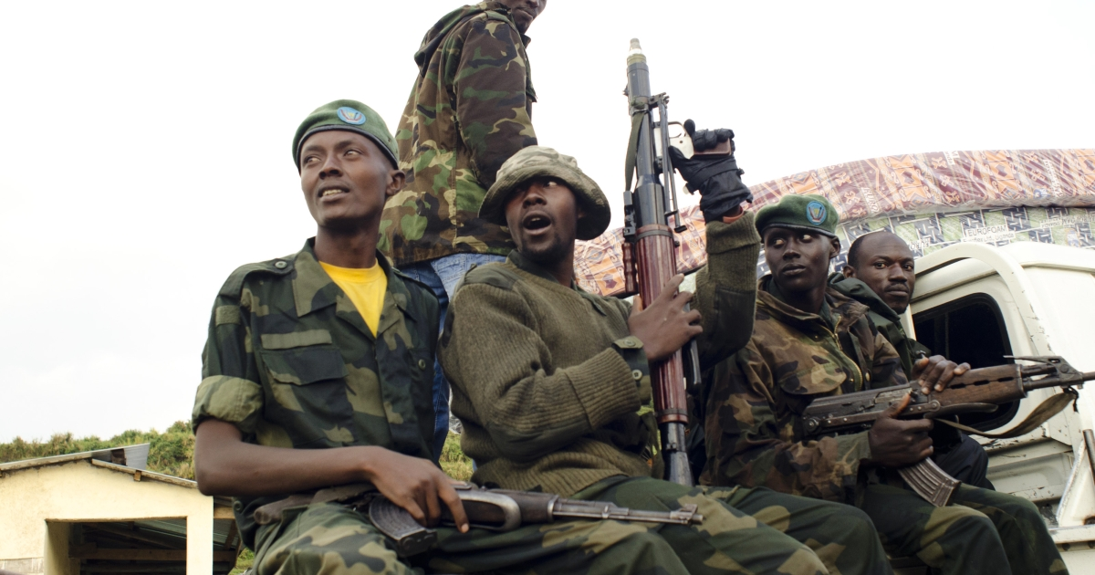 M23 rebels sit at the back of a pick-up truck captured a week before and formerly used by the Armed Forces of the Democratic Republic of Congo, as they carry supplies through Bunagana, on July 15, 2012.</p>